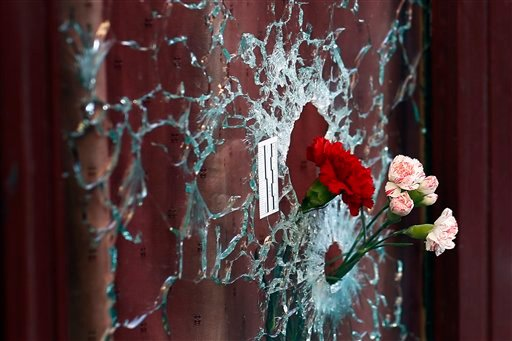 Flowers are set in a window shattered by a bullet at the Carillon cafe in Paris, France, Sunday Nov. 15, 2015, two days after over 120 people were killed in a series of shooting and explosions. French troops deployed around Paris on Sunday and tourist sit
