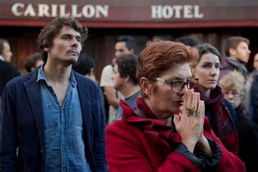 People pay their respect to the victims of the the attacks on restaurant Le Petit Cambodge (Little Cambodia) and the Carillon Hotel, rear, on the first of three days of national mourning in Paris, Sunday, Nov. 15, 2015. Thousands of French troops deployed