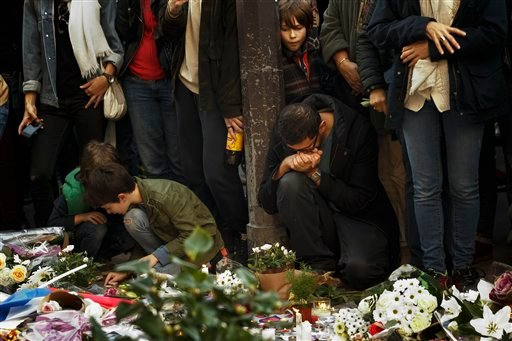 People pay their respects at the Carillon cafe in Paris, Sunday, Nov. 15, 2015. Thousands of French troops deployed around Paris on Sunday and tourist sites stood shuttered in one of the most visited cities on Earth while investigators questioned the rela
