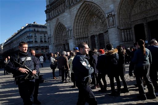 Policemen patrol in front of Notre Dame cathedral, following the Paris attacks, Sunday, Nov. 15, 2015. The Islamic State group claimed responsibility for Friday's attacks on a stadium, a concert hall and Paris cafes that left more than 120 people dead and