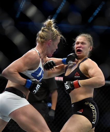 Holly Holm, left, punches Ronda Rousey during their UFC 193 bantamweight title fight in Melbourne, Australia, Sunday, Nov. 15, 2015. Holm pulled off a stunning upset victory over Rousey in the fight, knocking out the women's bantamweight champion in the s