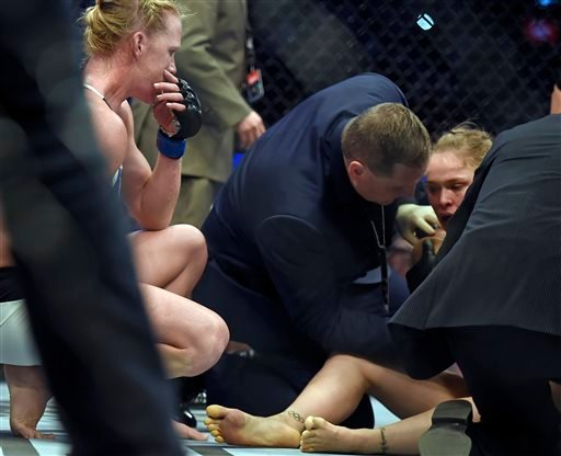 Holly Holm, left, watches Ronda Rousey, right, being tended after knocking her out during their UFC 193 bantamweight title fight in Melbourne, Australia, Sunday, Nov. 15, 2015. Holm pulled off a stunning upset victory over Rousey in the fight, knocking ou