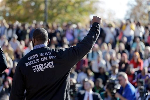 In this Nov. 9, 2015, file photo, a member of the black student protest group Concerned Student 1950 gestures while addressing a crowd following the announcement that University of Missouri System President Tim Wolfe would resign, at the university in Col
