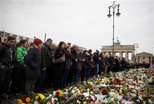 People stand still during a minute of silence at the Brandenburg Gate in Berlin, Germany, Monday, Nov. 16, 2015, to honor the victims of the terrorist attacks in France on Friday, Nov. 13, 2015.
