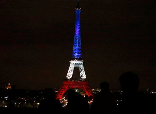 People watch the Eiffel Tower illuminated in the French national colors red, white and blue in honor of the victims of the terror attacks last Friday in Paris, Monday, Nov. 16, 2015.