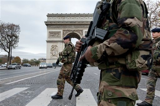 French soldiers cross the Champs Elysees avenue passing the Arc de Triomphe in Paris, Monday, Nov. 16, 2015.