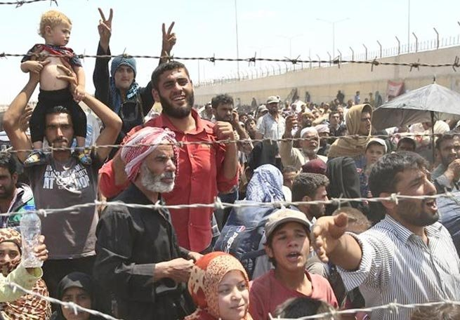 Syrian refugees mass at the Turkish border while fleeing intense fighting in northern Syria.