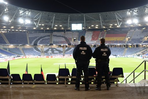 Two police officers stand in the HDI-Arena in Hannover, Germany, Tuesday, Nov. 17, 2015 just before the stadium was evacuated before the friendly soccer match between Germany and the Netherlands.