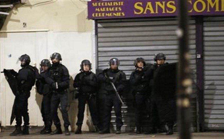 Authorities in the Paris suburb of Saint Denis are telling residents to stay inside during a large police operation near France's national stadium that two officials say is linked to last week's deadly attacks. (AP Photo/Francois Mori)