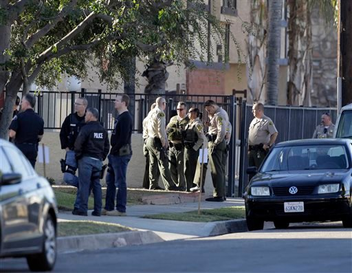 Law enforcement officers stand outside an apartment building, after suspects drove off from Downey police headquarters into the city of Montebello, Calif., on Thursday, Nov. 19, 2015. An officer was shot earlier to death while sitting in his car in the pa