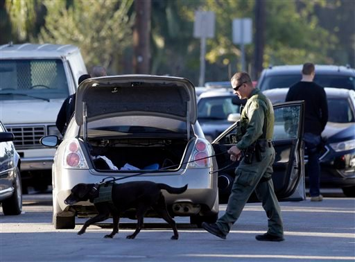 A K-9 police officer searches a vehicle after suspects drove off from Downey police headquarters into the city of Montebello, Calif., on Thursday, Nov. 19, 2015. An officer was shot earlier to death while sitting in his car in the parking lot of Downey po