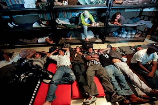 In this April 28, 2010, file photo, men look for a place to sleep in a crowded shelter for migrants deported from the United States, in the border city of Nogales, Mexico.