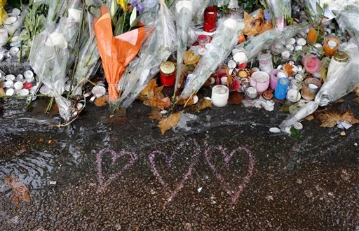 Hearts drawn and flowers lay on the pavement at a bar where an attack took place last week, Friday on, Friday, Nov. 20, 2015 in Paris.
