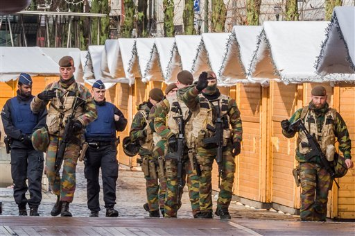 Belgian Army soldiers and policemen patrol near Christmas stalls in the center of Brussels on Sunday, Nov. 22, 2015. Western leaders stepped up the rhetoric against the Islamic State group on Sunday as residents of the Belgian capital awoke to largely emp