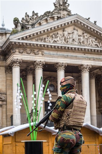A Belgian Army soldier patrols near Christmas huts in front of the old Brussels' stock exchange on Sunday, Nov. 22, 2015. Western leaders stepped up the rhetoric against the Islamic State group on Sunday as residents of the Belgian capital awoke to largel