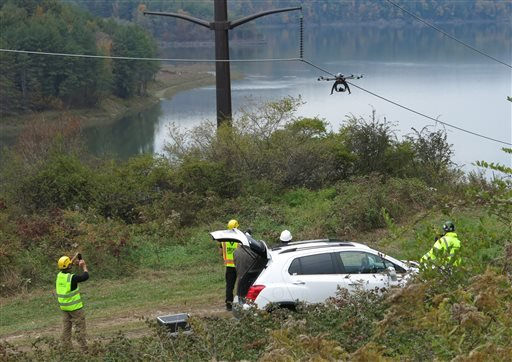 In a Wednesday, Oct. 21, 2015, photo, personnel from Boulder, Colo.-based bizUAS Corp. demonstrate the use of a Cyberhawk octocopter drone for power line inspections at a New York Power Authority hydroelectric generating site in the Catskills, near Blenhe