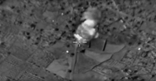 This photo made from the footage taken from Russian Defense Ministry official web site Monday, Nov. 23, 2015 shows an ammunition depot hit during the attack of Russian warplanes in Syria. Russia's President Vladimir Putin was in Tehran on Monday for talks