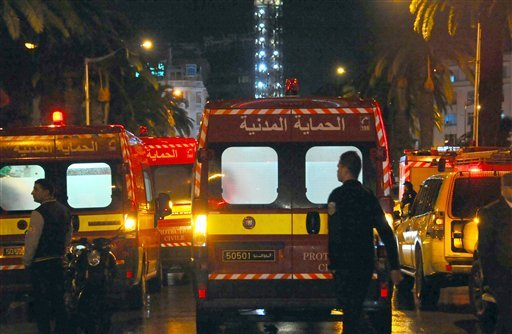 Ambulances and police vans are seen at the scene of a bus explosion in the center of the capital, Tunis, Tunisia, Tuesday, Nov. 24, 2015. An explosion hit a bus carrying members of Tunisia's presidential guard in the country's capital Tuesday, killing at