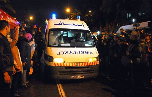 An ambulance rushes to the scene of a bus explosion in the center of the capital, Tunis, Tunisia, Tuesday, Nov. 24, 2015. An explosion hit a bus carrying members of Tunisia's presidential guard in the country's capital Tuesday, killing at least 12 people