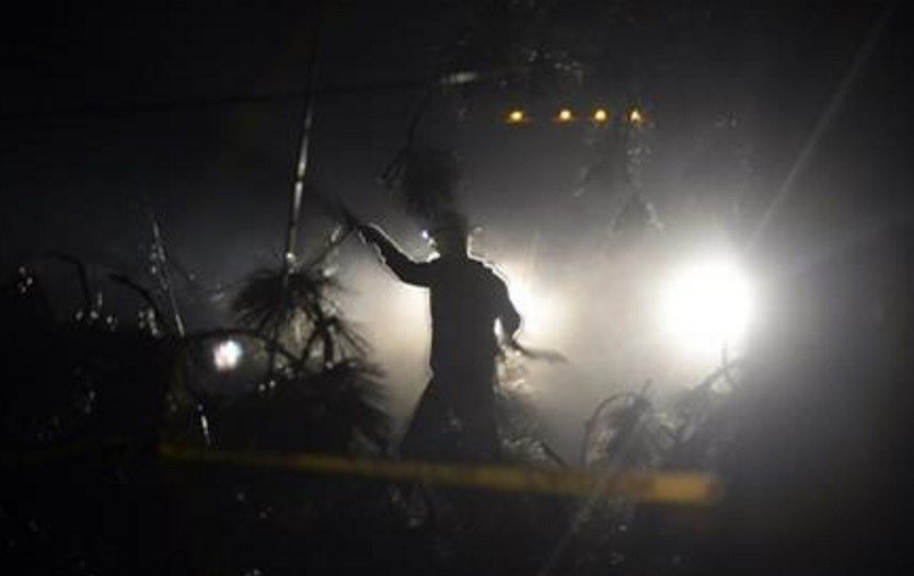 In this Nov. 20, 2015 photo, crews clear downed trees tangled in power and utility lines in Spokane, Wash., after deadly storms swept through the state leaving many without power. (Jesse Tinsley/The Spokesman-Review, via AP)