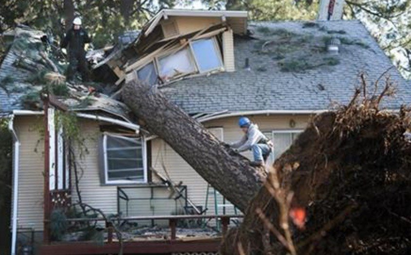 In this Nov. 21, 2015 photo, Jake Hines, left, and Ross Rukke, of Capstone Construction, work to remove a fallen tree in Spokane, Wash., after deadly storms swept through the state leaving many without power. (Dan Pelle/The Spokesman-Review, via AP)