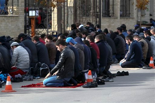 In this photo taken Friday, Nov. 13, 2015, men attend a Friday prayer at the mosque on Kotrova street in Dagestan's regional capital Makhachkala, Russia. An epidemic of recruitment for the Islamic State group has swept through the predominantly Muslim Dag