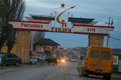 """In this photo taken Sunday, Nov. 15, 2015, an entrance to the village of Gubden with a sign reading """"Happy Travel. Gulden"""" is decorated with banner in colors of Russian and Dagestani flags, in the village of Gubden, Dagestan, Russia. An epidemic of recrui"""