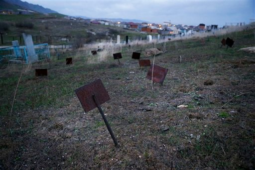 In this photo taken Friday, Nov. 13, 2015, metal plaques marking unidentified graves are at the cemetery on the outskirts of Dagestan's regional capital Makhachkala, Russia. Islamic militants killed in police raids in Dagestan are often buried in unmarked