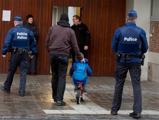 A man wheels a boy on his bicycle past police officers as they arrive for school in the center of Brussels on Wednesday, Nov. 25, 2015. Students in Brussels have begun returning to class after a two-day shutdown over fears that a series of simultaneous at