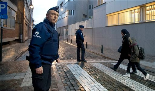 A woman and child pass by police officers as they arrive for school in the center of Brussels on Wednesday, Nov. 25, 2015. Students in Brussels have begun returning to class after a two-day shutdown over fears that a series of simultaneous attacks could b