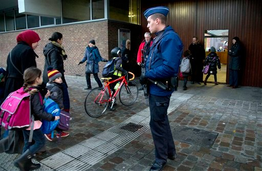 Children pass a police officer as they arrive for school in the center of Brussels on Wednesday, Nov. 25, 2015. Students in Brussels have begun returning to class after a two-day shutdown over fears that a series of simultaneous attacks could be launched