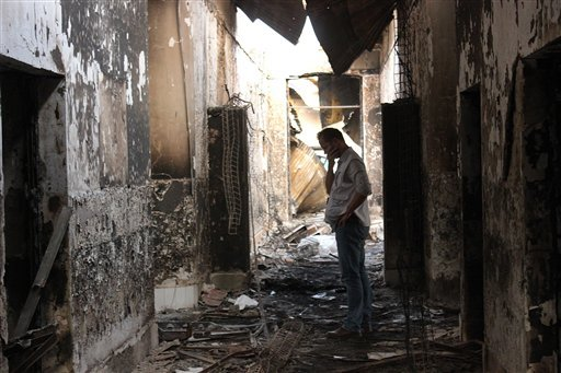 In this Friday, Oct. 16, 2015, file photo, an employee of Doctors Without Borders walks inside the charred remains of their hospital after it was hit by a U.S. airstrike in Kunduz, Afghanistan. An investigative report on the U.S. air attack that killed mo