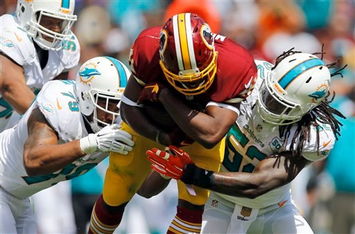 In this Sept. 13, 2015 file photo, Miami Dolphins defensive end Derrick Shelby (79) and middle linebacker Kelvin Sheppard (52) tackle Washington Redskins running back Alfred Morris (46) during the first half of an NFL football game in Landover, Md. They a