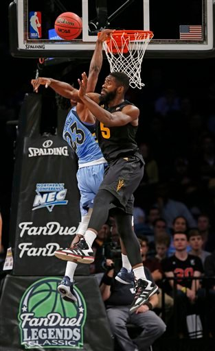 The FanDuel logo is visible, below, as Marquette guard Jajuan Johnson (23) defends Arizona State forward Obinna Oleka (5) during NCAA college basketball game in the FanDuel Legends Classic championship, Tuesday, Nov. 24, 2015, in New York. FanDuel and Dra