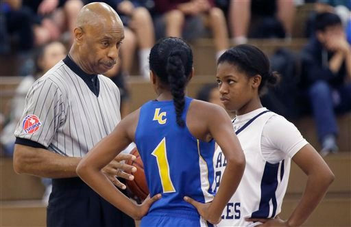 In this Thursday, Nov. 12, 2015, photo, Spenser Simmons, left, a referee with the North Texas Basketball Officials Association, speaks to players during a high school freshman girls basketball game in Allen, Texas. Violence against referees is as old as s