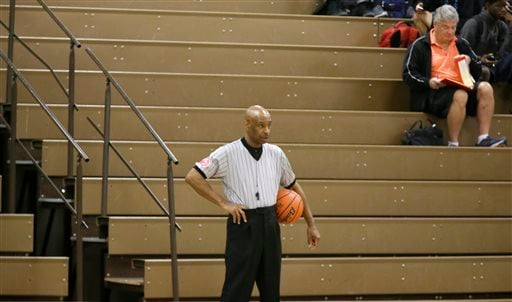 In this Thursday, Nov. 12, 2015, photo, Spenser Simmons, a referee with the North Texas Basketball Officials Association, stands ready during a break during a high school freshman girls basketball game in Allen, Texas. Violence against referees is as old