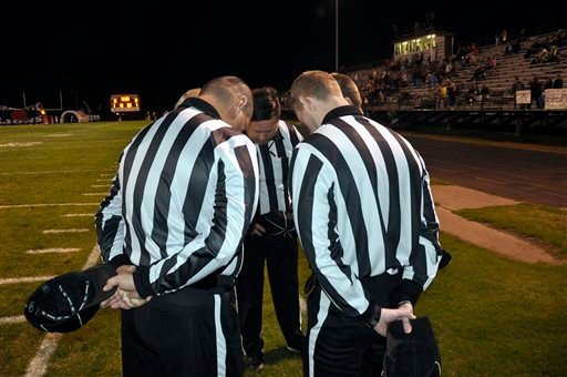 In this Friday, Nov. 6, 2015 photo, referee Greg Knight, center, leans in for a pre-game prayer with other officials before a high school football game in Gentry, Ark. Sports officials across the country are facing increasing scrutiny, with many taking ou
