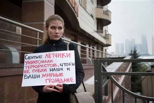 """A woman holds a poster as she pickets the Turkish Embassy in Moscow, Russia, Tuesday, Nov. 24, 2015. Russian President Vladimir Putin on Tuesday has called Turkey's decision to down a Russian jet near the Syria border a """"stab in the back."""" The poster read"""