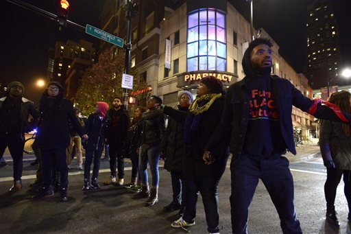 Protesters block a street during a protest for 17-year-old Laquan McDonald, Tuesday, Nov. 24, 2015, in Chicago. Chicago police Officer Jason Van Dyke,who shot McDonald 16 times last year, was charged with first-degree murder Tuesday, hours before th