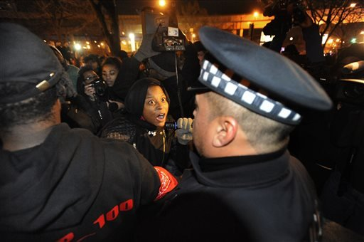 A protester yells at Chicago police officers outside the District 1 central headquarters at 17th and State streets, Tuesday, Nov. 24, 2015, in Chicago, during a protest for 17-year-old Laquan McDonald, who was fatally shot and killed in October 2014. Chic