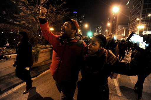 Protesters march during a protest, Tuesday, Nov. 24, 2015, in Chicago, for 17-year-old Laquan McDonald, who was fatally shot and killed in October 2014. Chicago police Officer Jason Van Dyke was charged Tuesday with first-degree murder in the killing. (AP
