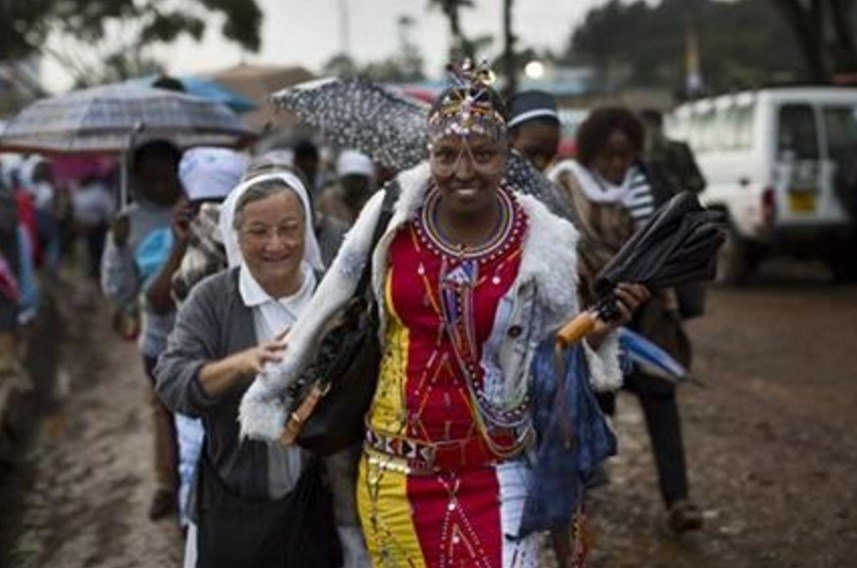 A Catholic sister and a Maasai woman arrive just after dawn in the rain and mud to attend a Mass to be given by Pope Francis at the campus of the University of Nairobi in Kenya Thursday, Nov. 26, 2015.
