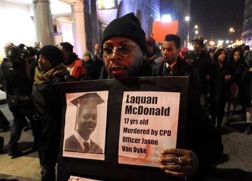 Nov. 24, 2015, file photo: A protester holds a sign as people rally for 17-year-old Laquan McDonald, who was shot 16 times by Chicago Police Department Officer Jason Van Dyke in Chicago. (AP Photo/Paul Beaty, File)