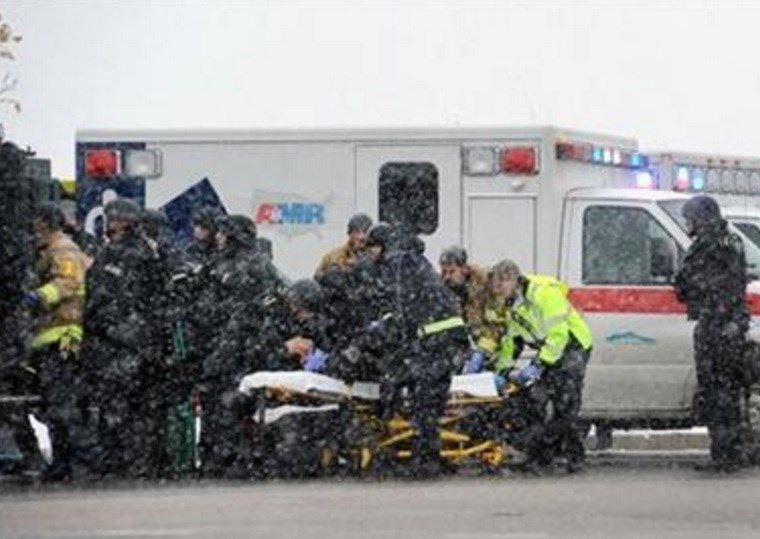 Emergency personnel transport an officer to an ambulance after reports of a shooting near the Planned Parenthood clinic Friday, Nov, 27, 2015, in Colorado Springs, Colo. (Daniel Owen/The Gazette via AP)