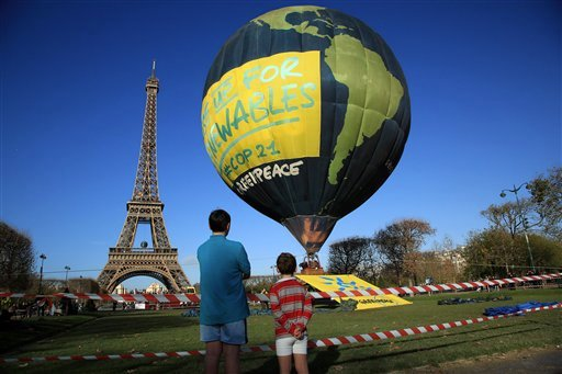 Boys look at a hot air balloon of the environmental group Greenpeace, near the Eiffel Tower ahead of the 2015 Paris Climate Conference, in Paris, Saturday, Nov. 28, 2015.