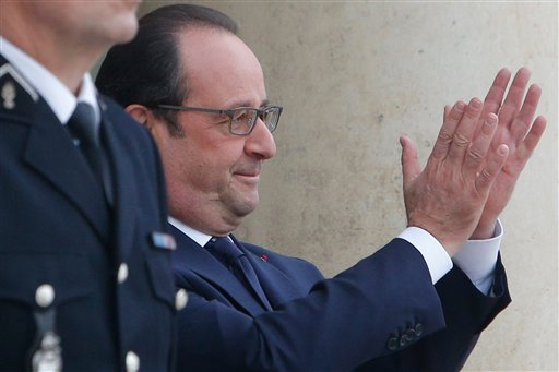 France's President Francois Hollande gestures as Secretary General of the United Nations Ban Ki-moon leaves the Elysee Palace, after a meeting, in Paris, Sunday, Nov. 29, 2015. More than 140 world leaders are gathering around Paris for high-stakes climate