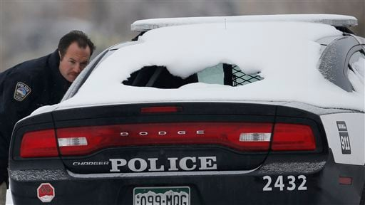 A crime scene investigator looks over a police vehicle damaged during Friday's shooting spree near a Planned Parenthood clinic Sunday, Nov. 29, 2015, in northwest Colorado Springs, Colo. (AP Photo/David Zalubowski)