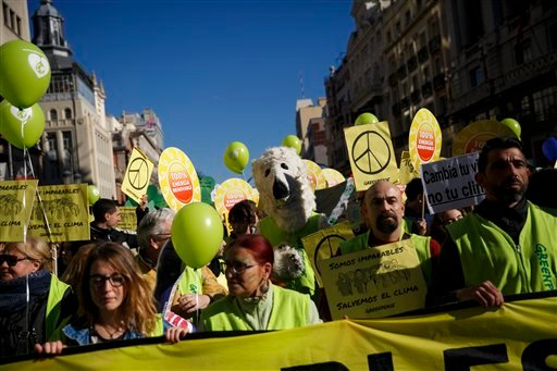 A protester dressed as a polar bear marches with others holding banners reading 'we are unstoppables, let's save the climate' through the streets of central Madrid during the Global Climate March, Sunday Nov. 29, 2015. More than 140 world leaders are gath