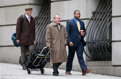 William Porter, right, one of six Baltimore city police officers charged in connection to the death of Freddie Gray, walks into a courthouse with his attorney Joseph Murtha, center Nov. 30, 2015, in Baltimore. (Rob Carr/Pool Photo via AP)