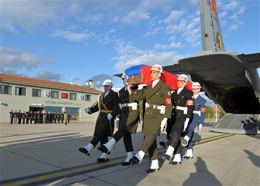 Turkish and Russian military officers, rear, salute as a Turkish honour guard carry the coffin of Russian pilot Lt. Col. Oleg Peshkov into a Russian Air Force transport plane at Esenboga Airport in Ankara, Turkey, Monday, Nov. 30, 2015. Early Saturday, Tu
